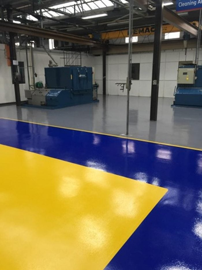 A blue and yellow finish on an epoxy factory floor